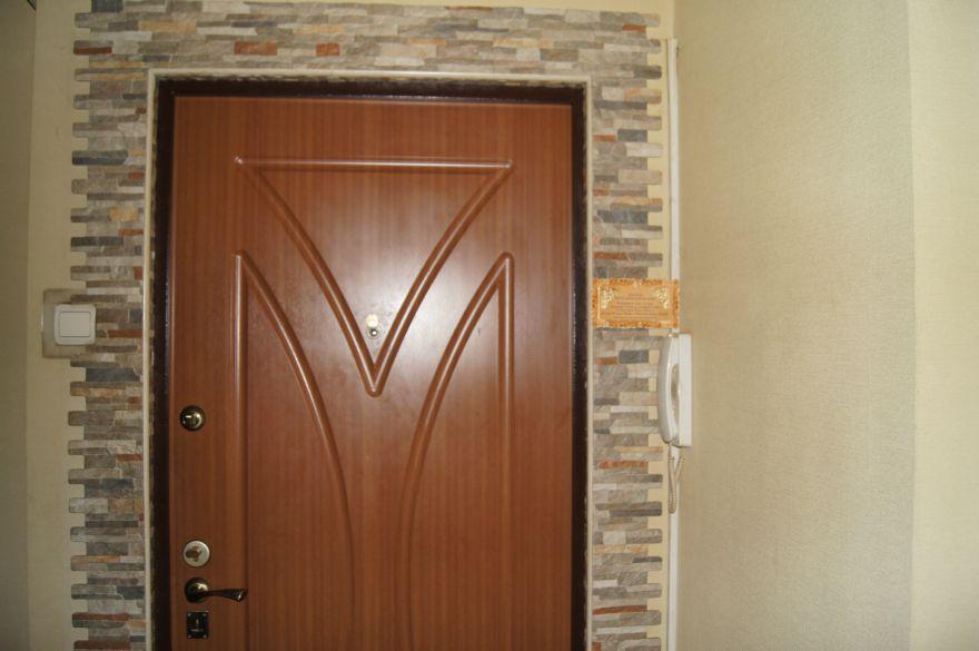 Фото отделка входной двери камнем